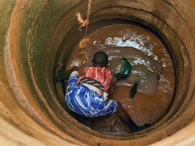 A Tanzanian teenager scoops up muddy water from a well. Many of the world's aquifers are being pumped out faster than they can replenish, a process that will increase sea level rise.